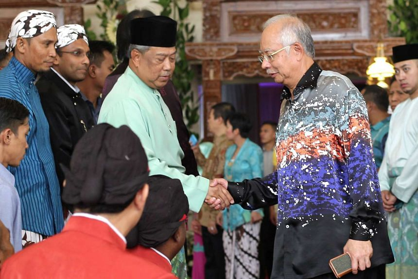 Malaysian PM Najib Razak (right) shaking hands with his deputy Muhyiddin Yassin during a wedding ceremony in June.