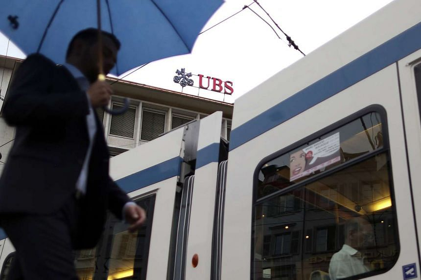 A pedestrian and a tram pass the UBS Group AG's headquarters in Zurich, Switzerland.