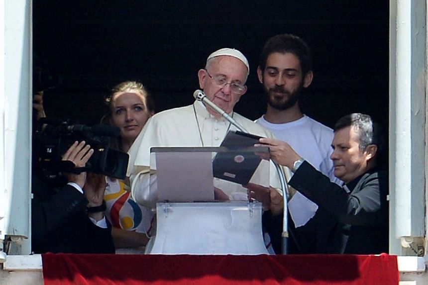 Pope Francis, accompanied by two Polish youths, uses an iPad to register online for the next 2016 World Youth Day in Poland.