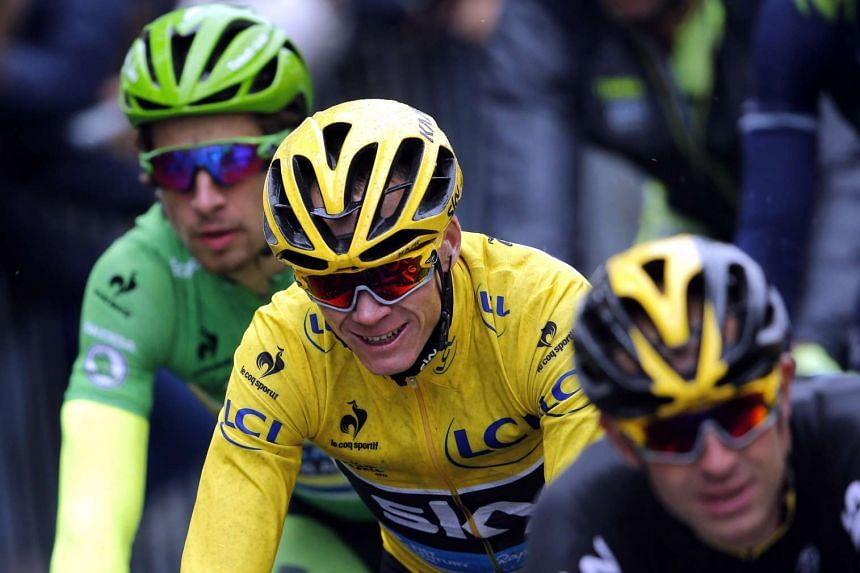 Team Sky rider Chris Froome, in the race leader's yellow jersey, reacts as he cycles on the Champs-Elysees avenue during the final stage of the Tour de France 2015.