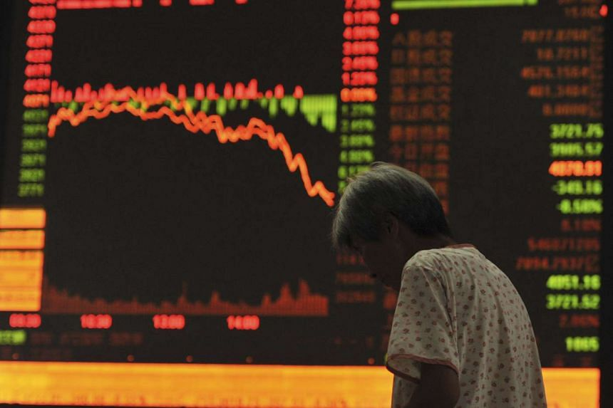An investor stands in front of an electronic board showing stock information at a brokerage house in Fuyang, Anhui province on July 27, 2015.