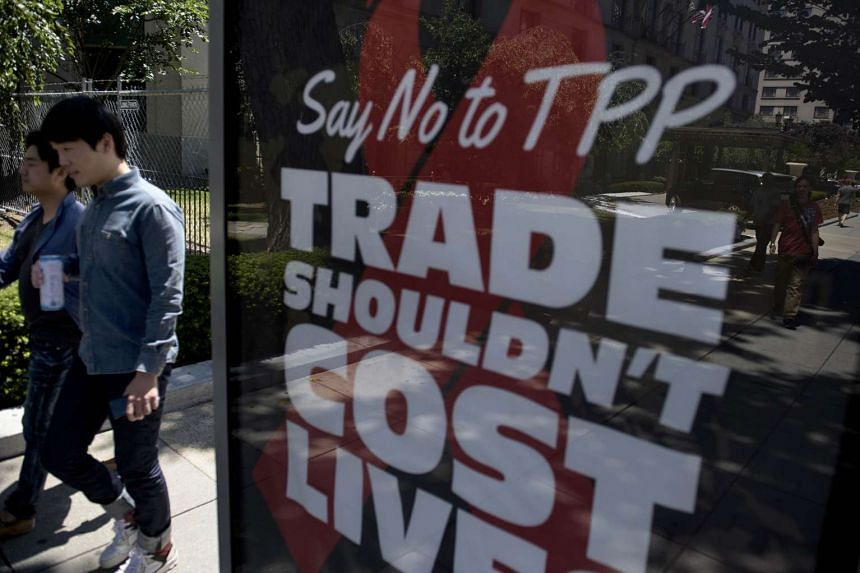 People pass an advertisement protesting the passage of the Trans-Pacific Partnership in Washington, DC.