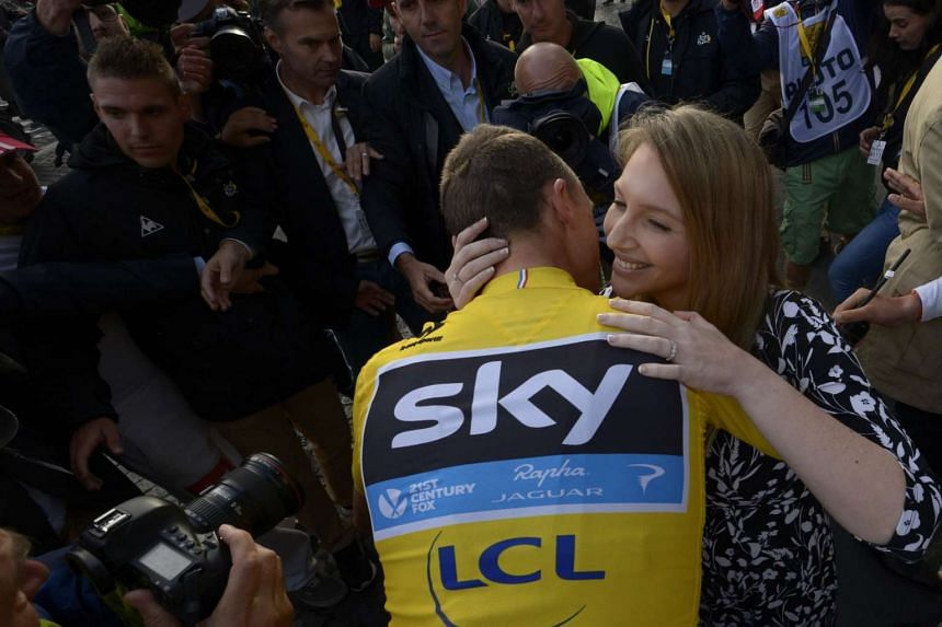 Froome (centre), wearing the overall leader's yellow jersey, kisses his wife Michelle Cound on the Champs-Elysees avenue in Paris at the end of the race.