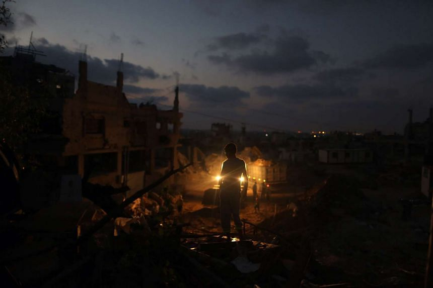 A Palestinian boy standing amidst the rubble of his home in al-Tufah, in the east of Gaza City, on July 27, 2015, during a power outage. Residents of Gaza, home to 1.8 million people, have been experiencing up to 15 hours of electricity outage a day