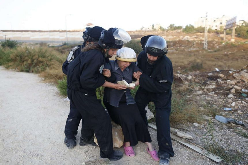 Female Israeli security forces dragging away an Israeli settler woman during the evacuation of a 24 housing units illegal building site where settlers had barricaded at the Jewish settlement of Beit El, near the West Bank town of Ramallah, early on J
