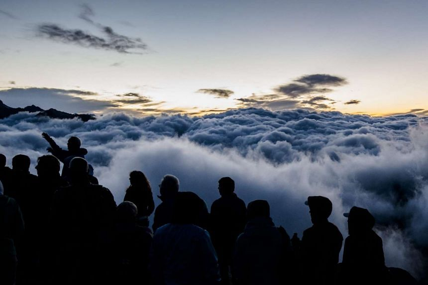 Tourists watching the sunrise above a sea of fog on Eggishorn mountain (2,927m above sea level), in Fiesch, Switzerland, early on July 28, 2015.