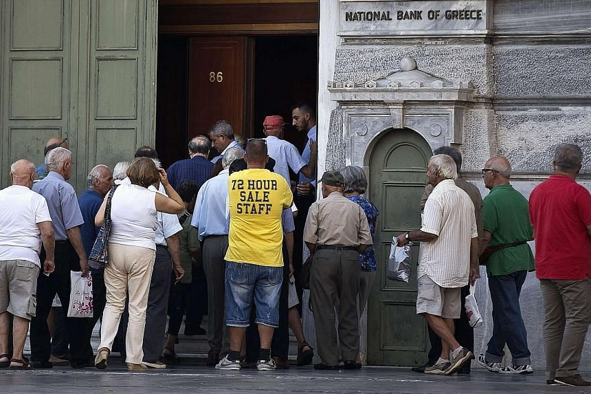Greeks gathering at a National Bank branch in Athens yesterday. While the government has relaxed some curbs on deposit withdrawals and capital controls for corporations, Greek proposals for a lifting of limits on trading have been rejected by the ECB