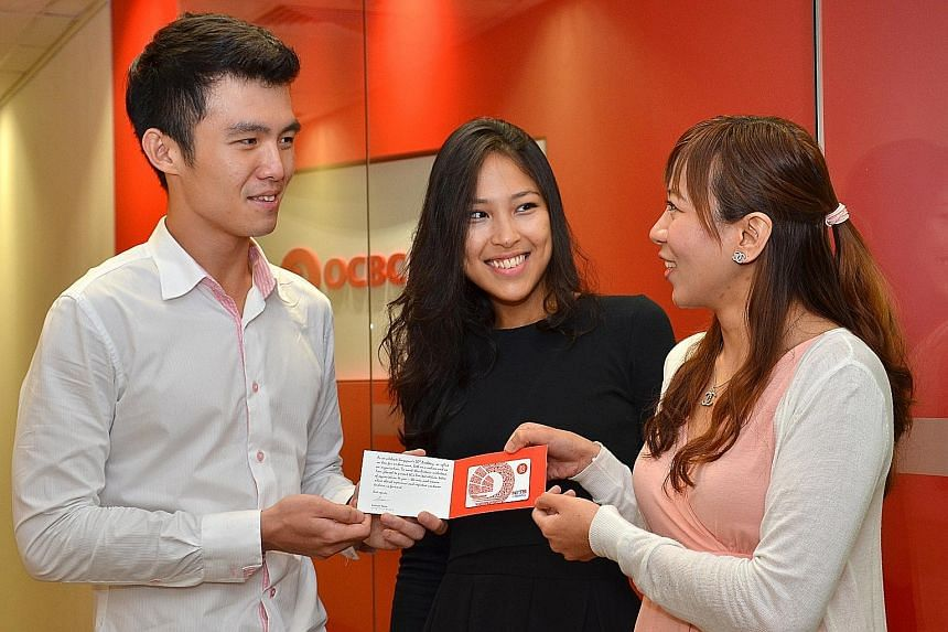 OCBC personnel (from far left) Mr Ben Chua, Ms Aisha Lin and Ms Jessica Huang with the exclusive SG50 Nets Flashpay card that all local staff will get, among other SG50 rewards. The bank will also set aside about $500,000 for its overseas staff to ho