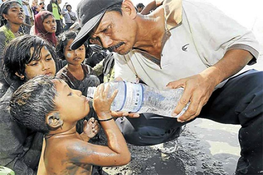 A villager helping a Rohingya boy in Alor Star, Malaysia. The country has been criticised for the Rohingya refugee crisis in South-east Asia.