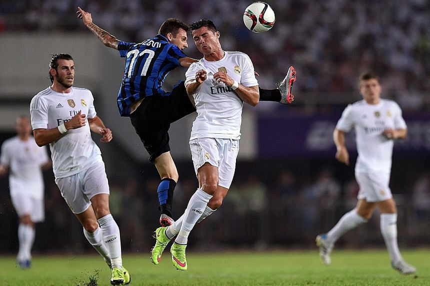 Real Madrid forward Cristiano Ronaldo (centre, in white) vying for the ball with Inter Milan's Jonathan Biabiany. Real won 3-0.