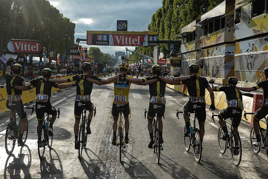 Chris Froome (centre), wearing the overall leader's yellow jersey, and his Sky team-mates head to the finish line to clinch the British team's third victory in four years. This year's Tour has been dogged by talk of possible doping by Froome but the