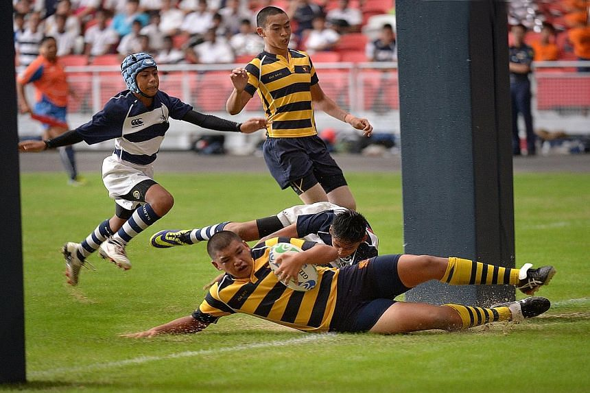 Anglo-Chinese School's (Independent) Tristan Yeow (with ball) scoring the first of his team's four tries as they beat St Andrew's School 28-8 in the C Division rugby final played at the new National Stadium on Aug 26 last year. Playing the occasional