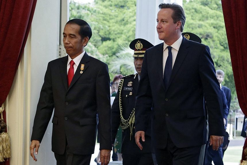 Indonesian President Joko Widodo (left) and British Prime Minister David Cameron arriving at the Presidential Palace in Jakarta yesterday. Mr Cameron arrives in Singapore today.