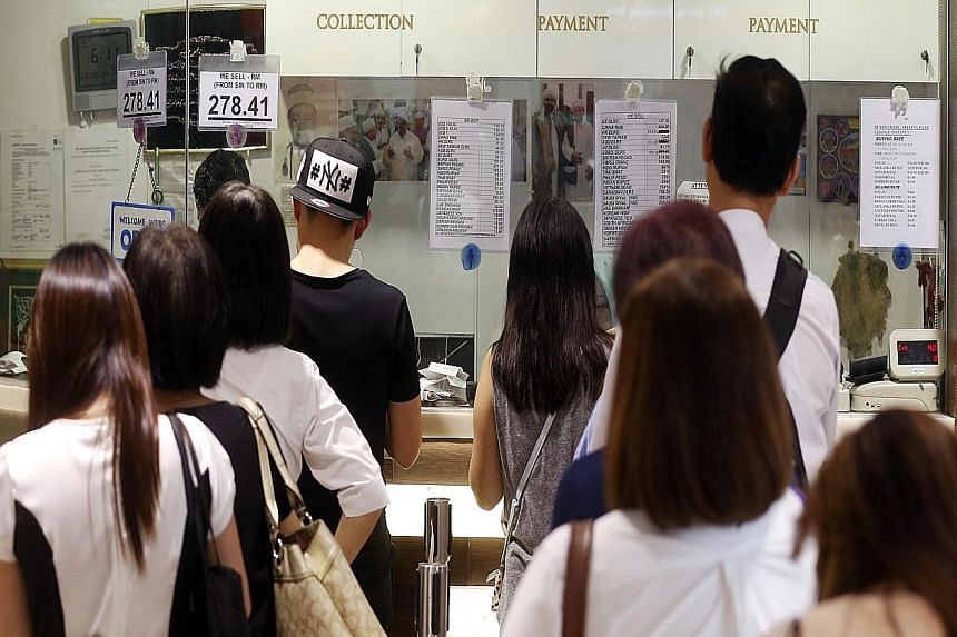Customers queueing at a money changer in Bishan yesterday evening, as the Australian dollar fell below the Singapore dollar and the Malaysian ringgit and Indonesian rupiah hit fresh lows against the US dollar.