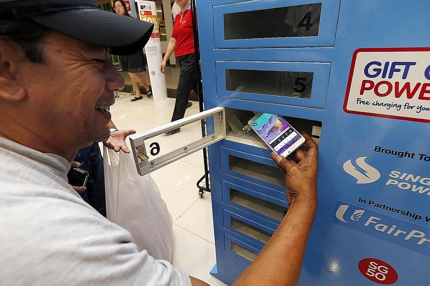 Mr Ridwan Hashim, 51, a delivery driver, charging his smartphone at a charging station in nex mall yesterday.