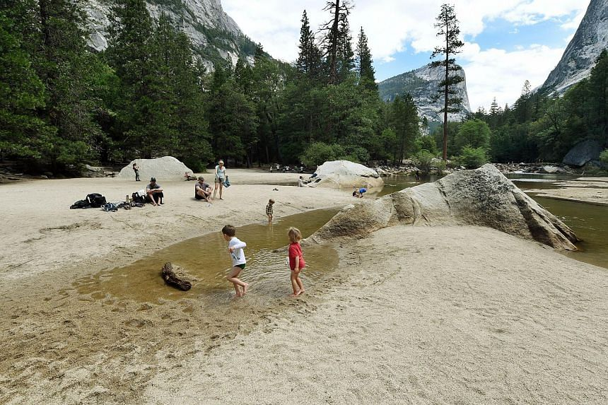 Children play on the exposed sandy bottom of Mirror Lake that is normally underwater and used by visitors to photograph reflections of the Half Dome rock monolith at Yosemite National Park in California on June 4, 2015.