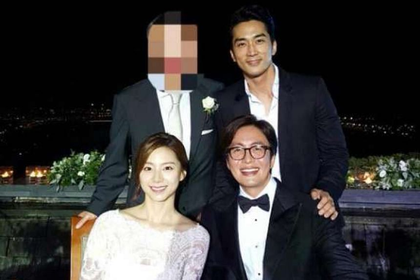 Actor Song Seung Heon (standing) with newlyweds Bae Yong Joon and Park Soo Jin at a rooftop banquet.