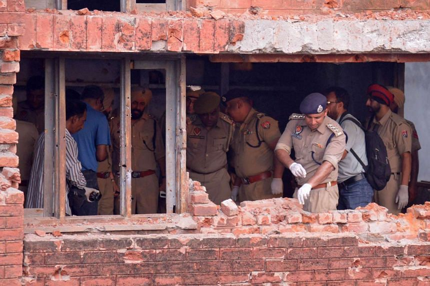 Indian police inspect a the building after armed militants attacked the police station in Dinanagar town, in the Gurdaspur district of Punjab state on July 27, 2015.