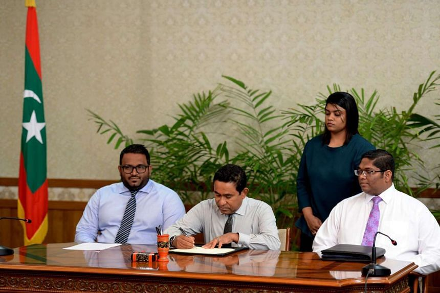 Maldivian President Abdulla Yameen (centre) approving a law allowing foreign ownership of land on July 23, 2015.