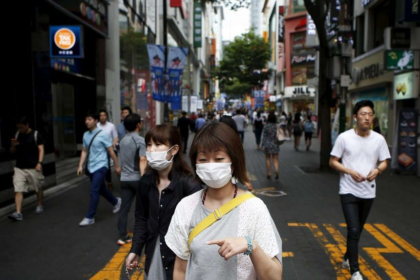 Women wearing masks to prevent contracting Middle East Respiratory Syndrome (Mers) walk at Myeongdong shopping district in central Seoul, South Korea, July 9, 2015. South Korea on Tuesday declared the end of its Mers outbreak, Yonhap news agency repo