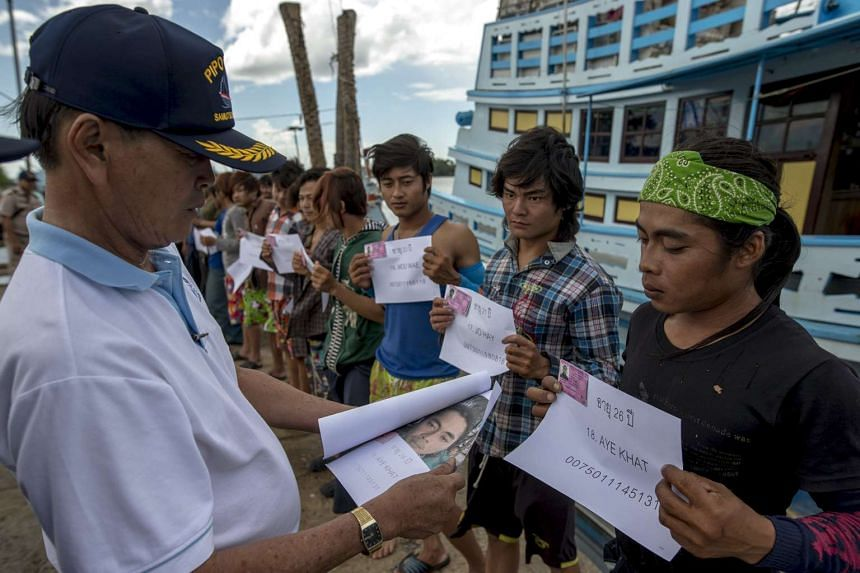 Migrant workers holding up their identity cards as a Thai authority officer checks them at a port in Samut Songkhram province, Thailand.
