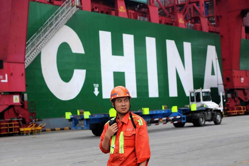 A worker looks on as containers are transported in Qingdao port, in east China's Shandong province, on July 1, 2015.