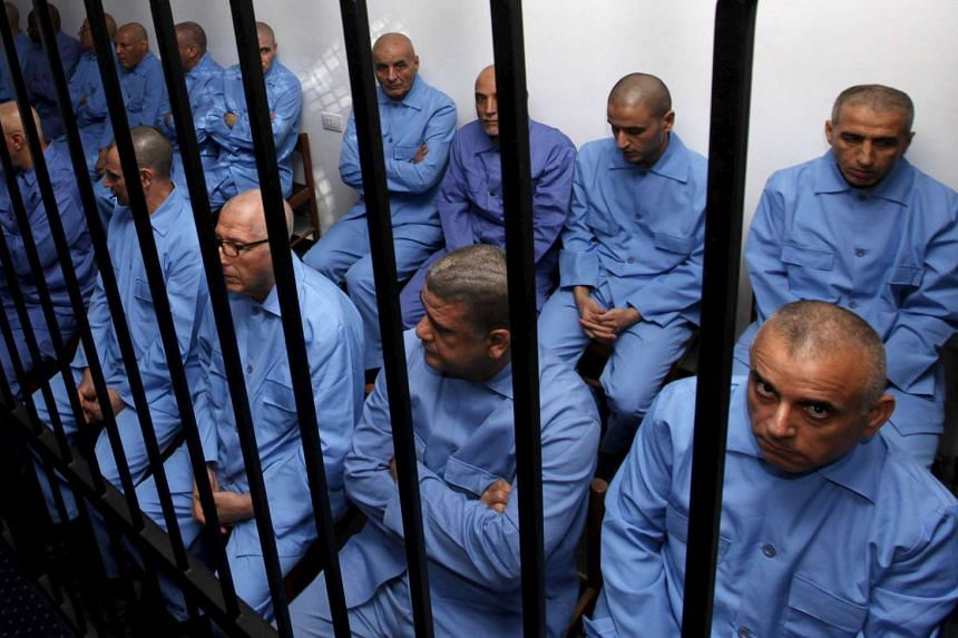 Former Gaddafi regime officials sit behind bars during a verdict hearing at a courtroom in Tripoli, Libya, on July 28, 2015.