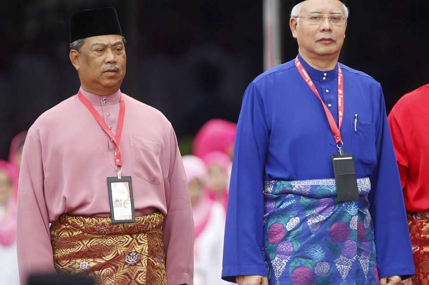 Najib Razak (right) and his deputy Muhyiddin Yassin stand in front of an honour guard during the opening of their country's ruling UMNO's annual gathering in Kuala Lumpur.