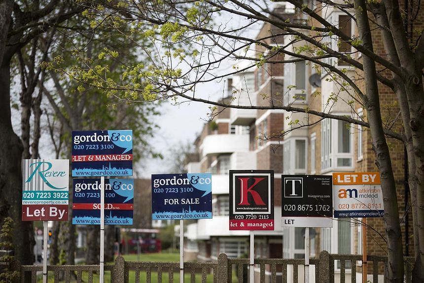 Real estate agents' signs standing outside a residential complex in London's Clapham district.