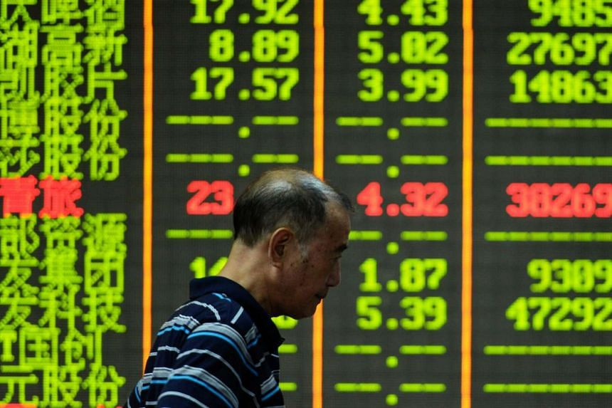 A man walking past a screen that shows share prices in a security firm in Hangzhou, east China's Zhejiang province.