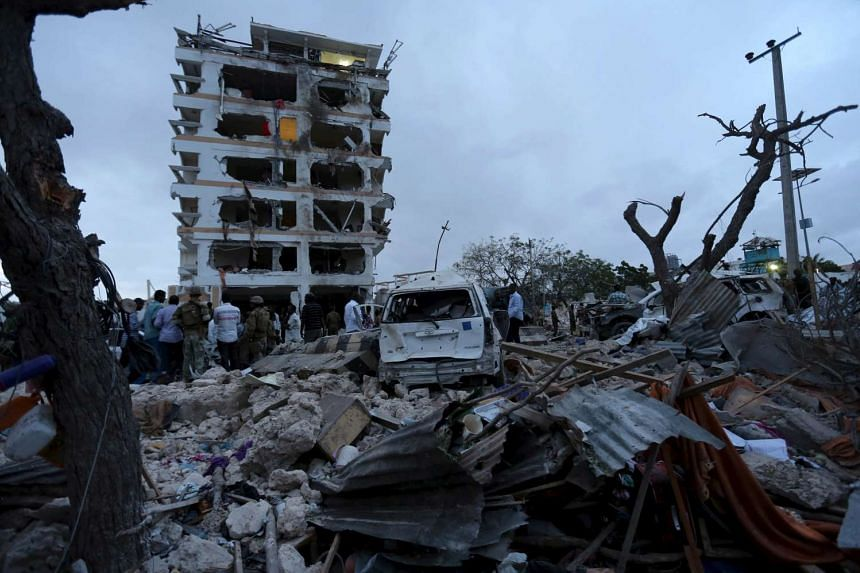 Somali government soldiers and local residents stand outside the ruins of the Jazeera hotel after an attack in Somalia's capital Mogadishu, on July 26, 2015.