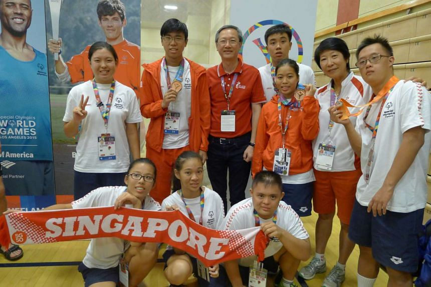 Minister of State for Culture, Community and Youth Sam Tan (centre, in red) with swimmer Bryan James Seow (standing, extreme right), Team Singapore swimmers and Dr Teo-Koh Sock Miang, President, Special Olympics Singapore (second from right).