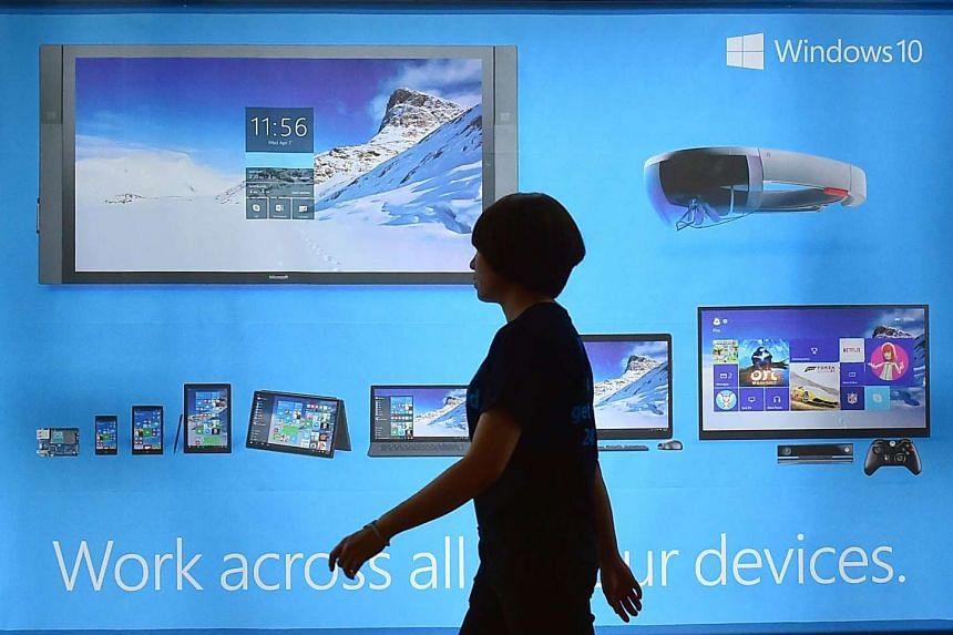 A woman walks past a billboard for Windows 10 in Seoul, South Korea on July 29, 2015.
