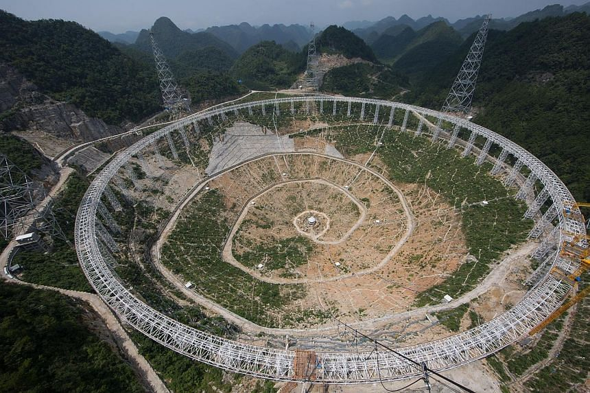 China is building the world's biggest radio telescope. Seen here under construction in Guizhou, the 500m-aperture spherical telescope's enormous dish is larger than 30 football fields, and will be connected to one of the world's fastest computers to