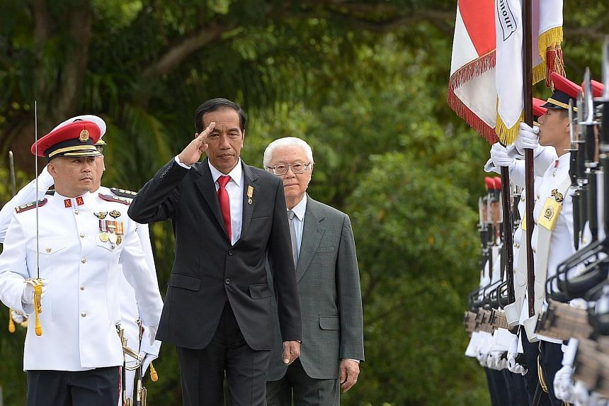 """Indonesian President Joko Widodo saluting as he inspected an honour guard with President Tony Tan Keng Yam during a welcome ceremony at the Istana yesterday. Mr Joko urged investors to look to Indonesia, where he says """"a new economic cycle is beginni"""