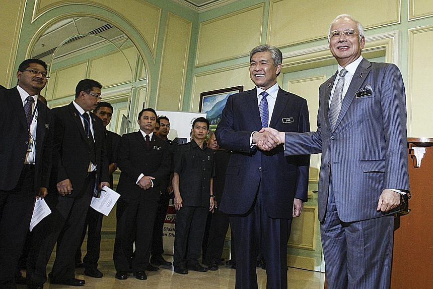 Malaysian Prime Minister Najib Razak (right) with his new deputy, Datuk Seri Ahmad Zahid Hamidi, after a press conference on the reshuffling of his Cabinet at the Prime Minister's Office in Putrajaya yesterday. The reshuffle was widely condemned by g