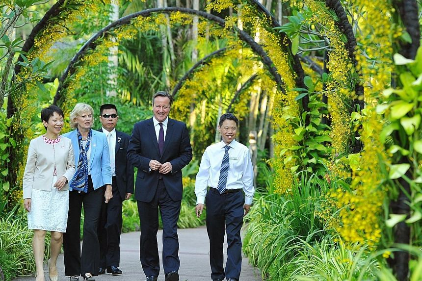 Mr David Cameron (centre) in the National Orchid Garden yesterday with (from left) Ms Grace Fu, Minister in the Prime Minister's Office; Britain's Minister for Small Business Anna Soubry; and Mr Kenneth Er, CEO of National Parks Board. The British le