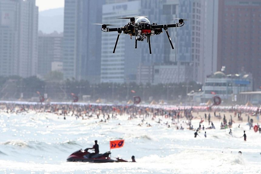 A public safety drone hovering above Haeundae beach in Busan yesterday. The Busan city government is using the drones at the popular beach as one of its safety measures to prevent drownings during the busy school holiday period, which typically runs