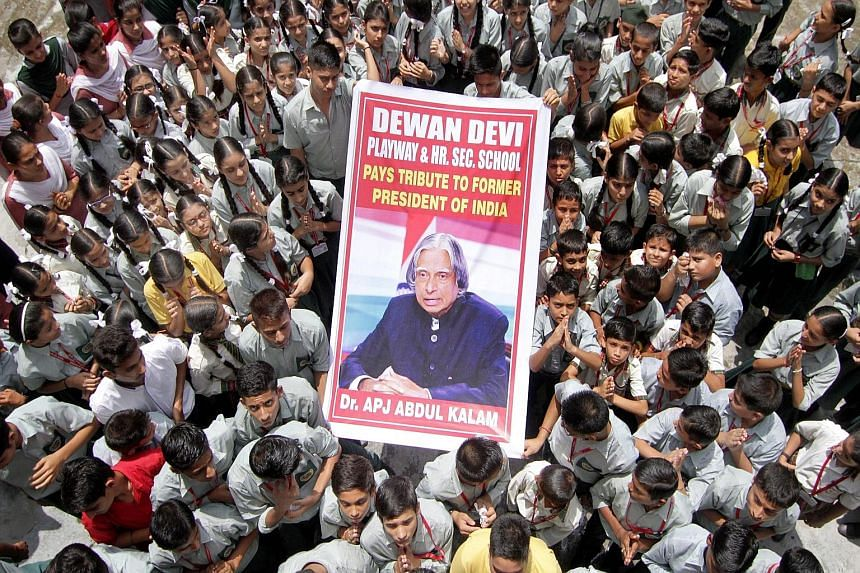 Indian schoolchildren holding up a portrait of Dr A.P.J. Abdul Kalam as they paid tribute to him in Jammu, India, yesterday.