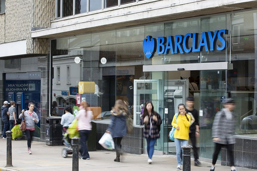 Pedestrians pass a Barclays bank, operated by Barclays Plc, in Guildford, UK, on July, 27, 2015.