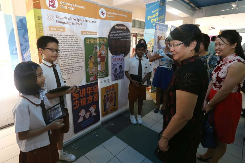 Two pupils from Ahmad Ibrahim Primary presenting their school's e-book entry, on Singapore's Speak Mandarin Campaign in 1979, to guests.
