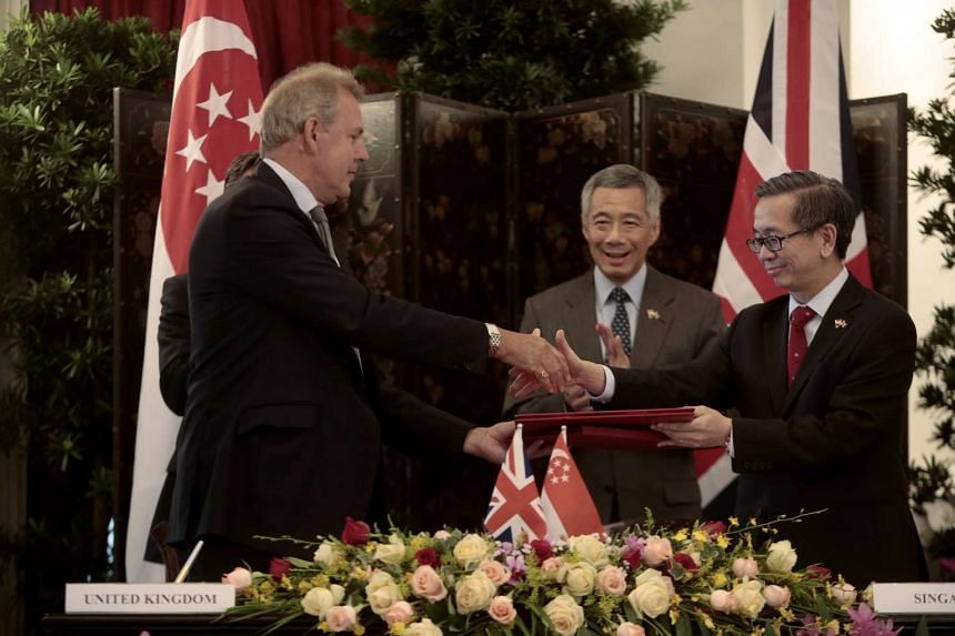 British National Security advisor Sir Nigel Kim Darroch (left) and Chief Executive of the Cyber Security Agency of Singapore David Koh (right) exchange documents after signing the MOU.