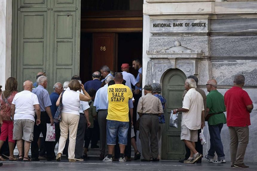 People enter a National Bank branch following its opening in Athens, Greece, on July 27, 2015.