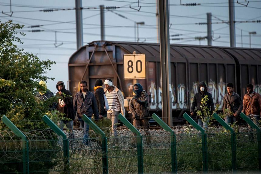 Migrants who successfully crossed the Eurotunnel terminal walk on the side of the railroad as they try to reach a shuttle to Great Britain, on July 28, 2015 in Frethun, northern France.