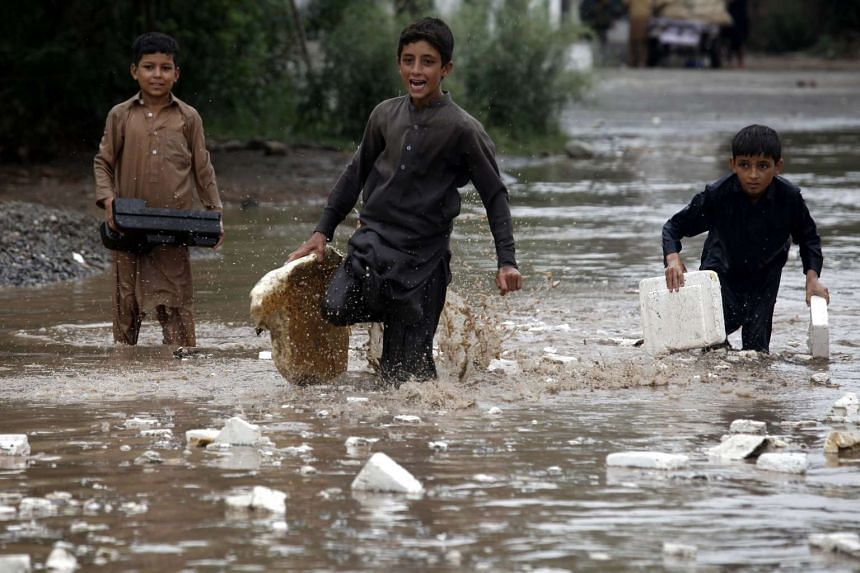 Children flee flooded areas in the Charsadda district of Khyber Pakhtunkhwa province, Pakistan.
