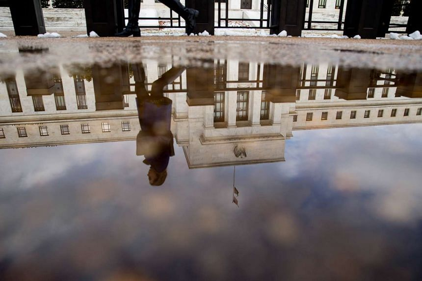 A woman walks past the Marriner S. Eccles Federal Reserve building as it is reflected in a puddle of water in Washington, US.