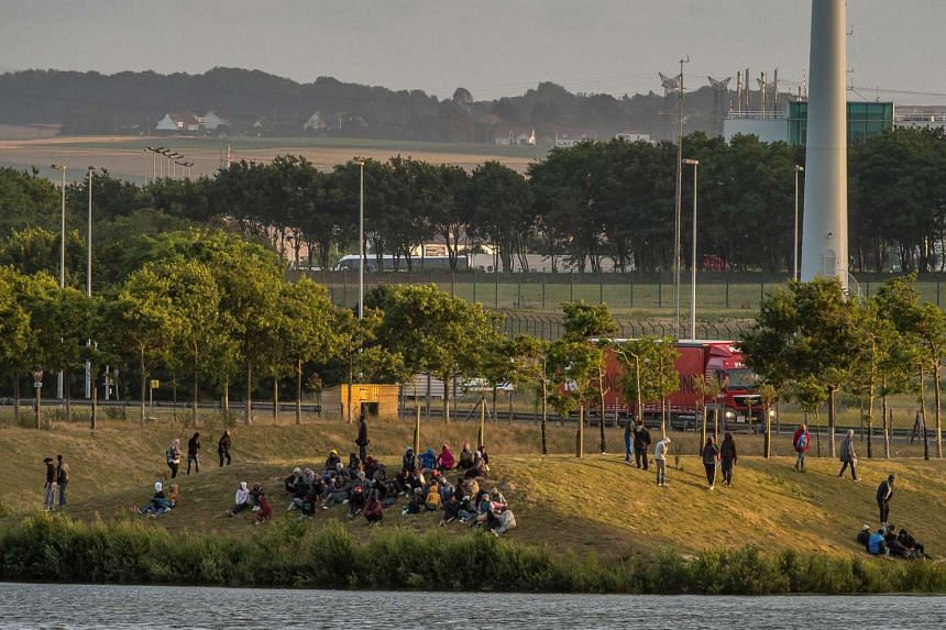 Migrants gather near the Eurotunnel terminal to try to climb in a shuttle heading to Britain.