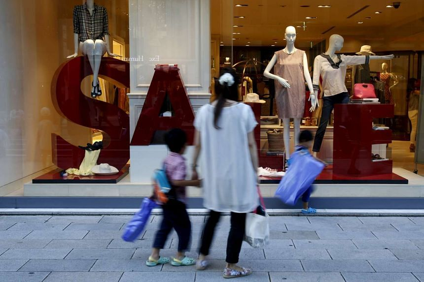A woman and her children walk past a display window outside a luxury brand store at Tokyo's Ginza shopping district, Japan, July 20, 2015.