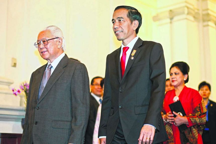 Indonesian President Joko Widodo (right) walks with his Singaporean counterpart Tony Tan (left) to a meeting at the Istana in Singapore July 28, 2015.
