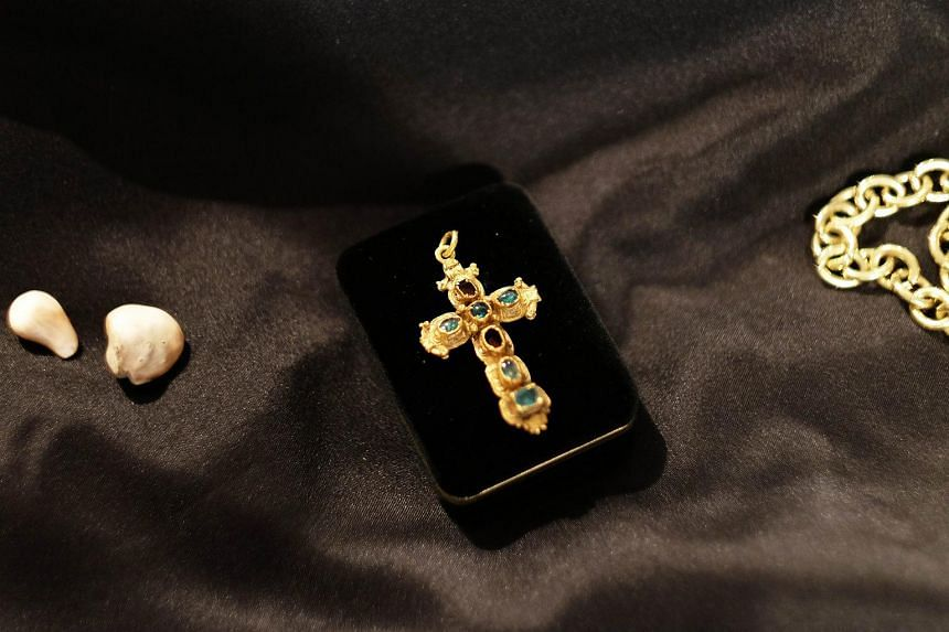 An an emerald-encrusted crucifix (centre) is pictured along with other Spanish treasures at the Guernsey's in New York on July 6, 2015.